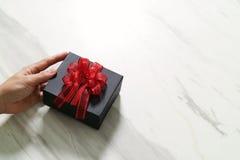 regalo que da, mano del hombre que sostiene una caja de regalo en un gesto de dar o Foto de archivo