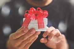 regalo que da, mano del hombre que sostiene una caja de regalo en un gesto del donante B Foto de archivo libre de regalías