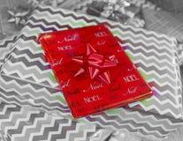 Regalo rojo de la Navidad envuelto en el papel de Noel, color aislado en blac Imagen de archivo libre de regalías