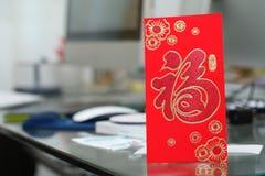 Regalo rojo del sobre en trabajo de la tabla del Año Nuevo chino Imagen de archivo