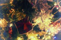 Regalo rojo en una rama del árbol del Año Nuevo Foto de archivo libre de regalías