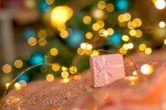 Regalo rosado en un fondo coralino contra un árbol borroso del Año Nuevo imagen de archivo