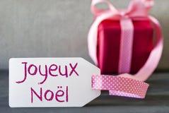 Regalo rosado, etiqueta, Joyeux Noel Means Merry Christmas Imagen de archivo libre de regalías