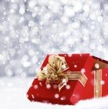 Regalo rosso di Natale con i fiocchi di neve di caduta Fotografia Stock Libera da Diritti