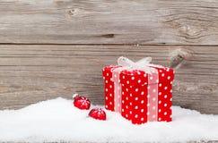Regalo rosso di Natale con neve Fotografie Stock