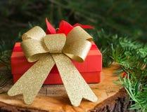 Regalo rosso di Natale sul fondo dell'albero e di legno Fotografia Stock