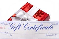 Regalo rosso luminoso con un certificato di regalo Fotografia Stock