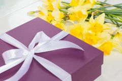 Regalo, scatola porpora con il nastro bianco e fiori gialli fotografie stock libere da diritti