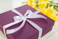 Regalo, scatola porpora con il nastro bianco e fiori gialli immagini stock