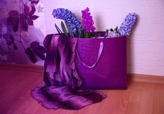 Regalo ultravioleta con tres jacintos púrpuras y una bufanda violeta Imagenes de archivo