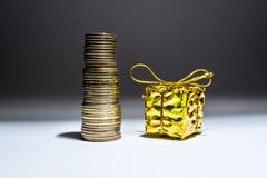 Regalo in un contenitore di oro con un arco su un mucchio del primo piano della colonna delle monete di oro su fondo in bianco e  Fotografia Stock Libera da Diritti