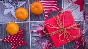 Regalo in una scatola rossa con la decorazione ed i mandarini Fotografia Stock Libera da Diritti