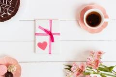 Regalo a Valentine& x27; día de s, con té y flores en un fondo blanco Visión superior, efecto de la película Foto de archivo