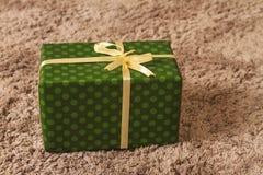 Regalo verde del nuovo anno e di Natale sotto l'albero sulla coperta Immagini Stock
