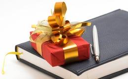 Regalo y cuaderno rojos con la pluma imagen de archivo libre de regalías