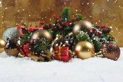 Regalo y decoraciones de la Navidad acurrucados en nieve Imágenes de archivo libres de regalías