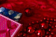 Regalo y guirnalda de la Navidad hechos de pequeñas gotas rojas En un fondo rojo Juguete del Año Nuevo Fotos de archivo libres de regalías