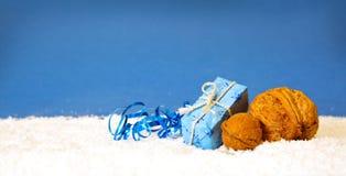 Regalo y nuez de la Navidad en fondo azul Imagenes de archivo