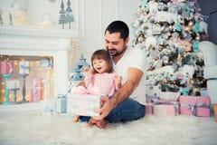 Regalos abiertos del ` s del Año Nuevo del padre grande y de la pequeña hija feliz cerca del árbol de navidad Fotografía de archivo