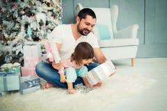 Regalos abiertos del ` s del Año Nuevo del padre grande y de la pequeña hija feliz cerca del árbol de navidad Fotografía de archivo libre de regalías