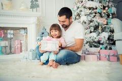 Regalos abiertos del ` s del Año Nuevo del padre grande y de la pequeña hija feliz cerca del árbol de navidad Fotos de archivo