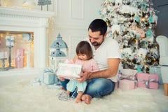 Regalos abiertos del ` s del Año Nuevo del padre grande y de la pequeña hija feliz cerca del árbol de navidad Fotos de archivo libres de regalías