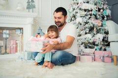 Regalos abiertos del ` s del Año Nuevo del padre grande y de la pequeña hija feliz cerca del árbol de navidad Imágenes de archivo libres de regalías
