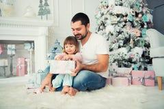 Regalos abiertos del ` s del Año Nuevo del padre grande y de la pequeña hija feliz cerca del árbol de navidad Imagenes de archivo