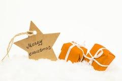 Regalos anaranjados en la nieve blanca y una estrella con la Feliz Navidad de la inscripción imagen de archivo