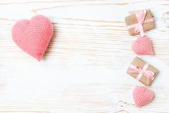 Regalos atados con una cinta rosada y corazones hechos punto en un fondo de madera blanco Imagen de archivo