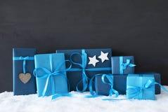Regalos azules de la Navidad, pared negra del cemento, nieve Fotos de archivo