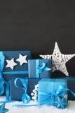 Regalos azules verticales de la Navidad, pared negra del cemento, nieve Fotos de archivo
