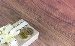 Regalos Bitcoins en una caja de regalo del estilo del vintage en un fondo de madera rústico Foto de archivo