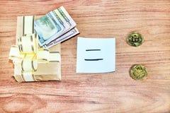 Regalos Bitcoins en una caja de regalo del estilo del vintage en un fondo de madera rústico y un signo de igualdad o una flecha U Imagen de archivo
