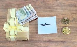 Regalos Bitcoins en una caja de regalo del estilo del vintage en un fondo de madera rústico y un signo de igualdad o una flecha U Fotos de archivo libres de regalías