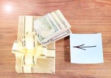 Regalos Bitcoins en una caja de regalo del estilo del vintage en un fondo de madera rústico y un signo de igualdad o una flecha U Foto de archivo