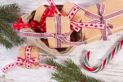 Regalos con las cintas para la Navidad o las tarjetas del día de San Valentín en bolso del yute y ramas spruce Imágenes de archivo libres de regalías