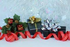 Regalos con los arcos brillantes en una decoración de la fiesta de Navidad Imagenes de archivo