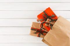 Regalos creativos de la Navidad en bolsa de papel en el fondo de madera blanco de la tabla Fotos de archivo libres de regalías