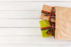 Regalos creativos de la Navidad en bolsa de papel en el fondo de madera blanco de la tabla Fotografía de archivo libre de regalías