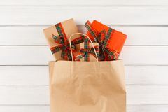 Regalos creativos de la Navidad en bolsa de papel en el fondo de madera blanco de la tabla Fotografía de archivo