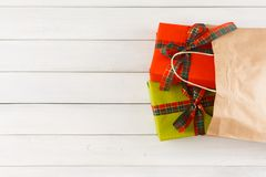 Regalos creativos de la Navidad en bolsa de papel en el fondo de madera blanco de la tabla Imagen de archivo