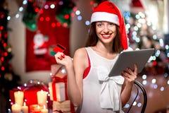 Regalos de compra de la mujer joven con la tarjeta de crédito encendido Imágenes de archivo libres de regalías