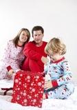 Regalos de la apertura de la familia en la Navidad Imágenes de archivo libres de regalías