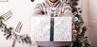 Regalos de la explotación agrícola del hombre joven delante del árbol de navidad Imagen de archivo