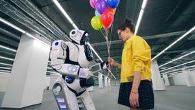 Regalos de la muchacha al manojo de globos a su droid del amigo en un cuarto almacen de metraje de vídeo