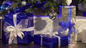 Regalos de la Navidad debajo de un árbol con los fuegos de las velas en los regalos de la Nochebuena a los queridos en la recogid metrajes