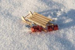 Regalos de la Navidad del trineo caido en la nieve Fotos de archivo
