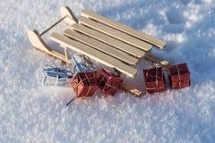 Regalos de la Navidad del trineo caido en la nieve Foto de archivo