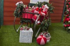 Regalos de la Navidad dentro del trineo, con las flores y el árbol adornado Imagen de archivo